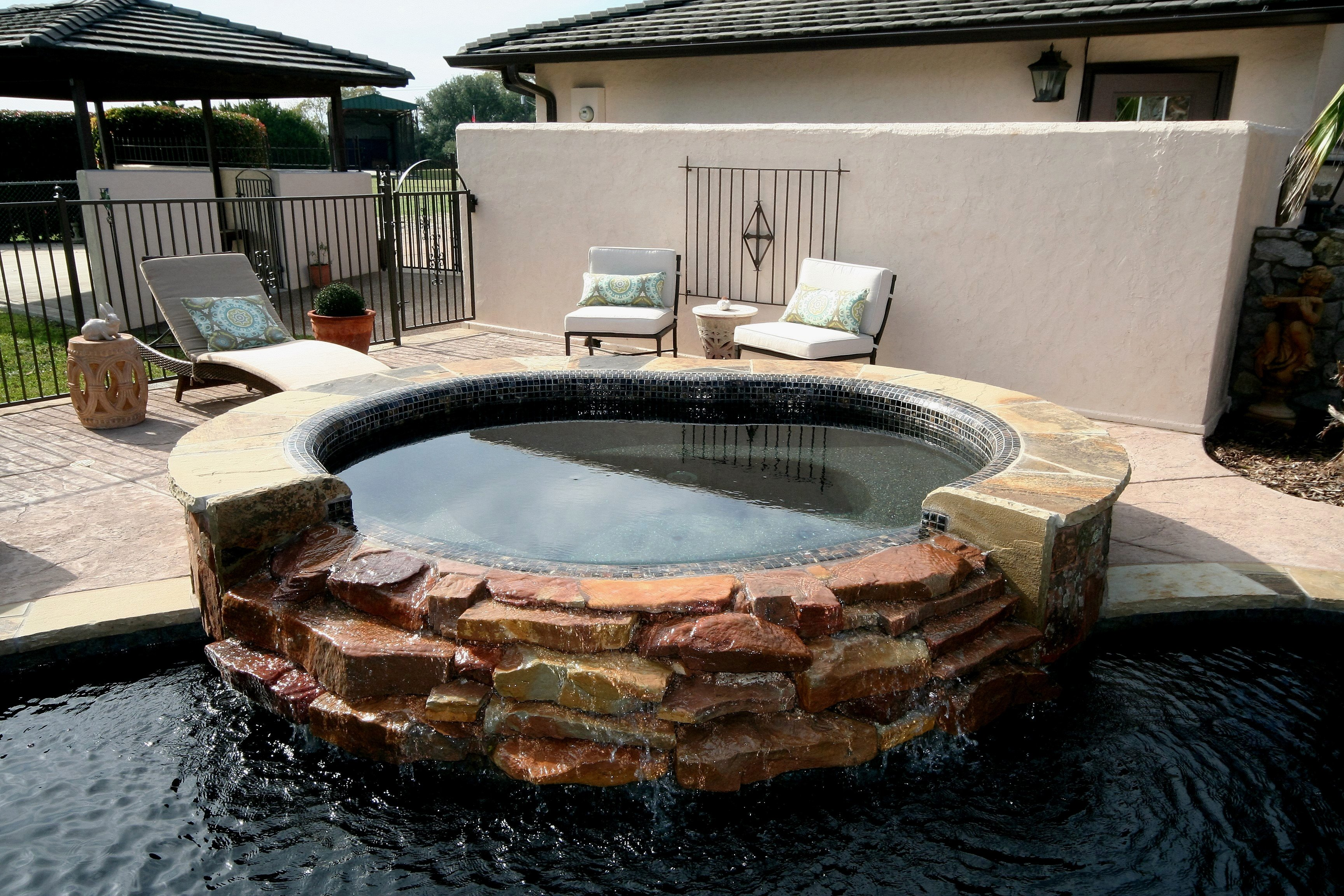 Spa with rolled beam tile with cascading spillway, Oklahoma flagstone, Stamped Concrete, Wet Edge Jet Black plaster, & Zodiac Equipment