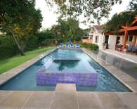 Straight-line Pool; Vanishing Edge Glass Tiled Spa, Deck Fountains, Wet Edge Plaster, Zodiac Equipment