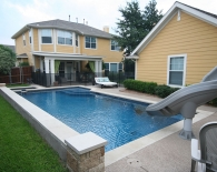 Geometric Pool and Spa; Interfab Slide, Raised Water Feature, Sundek, Kiddie Fence, Wet Edge Plaster, Zodiac Equipment