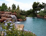Free Form Vanishing Edge Pool and Attached Spa, Rock Waterfall, Grotto, Aggregate Decking, Wet Edge Plaster, Zodiac Equipment