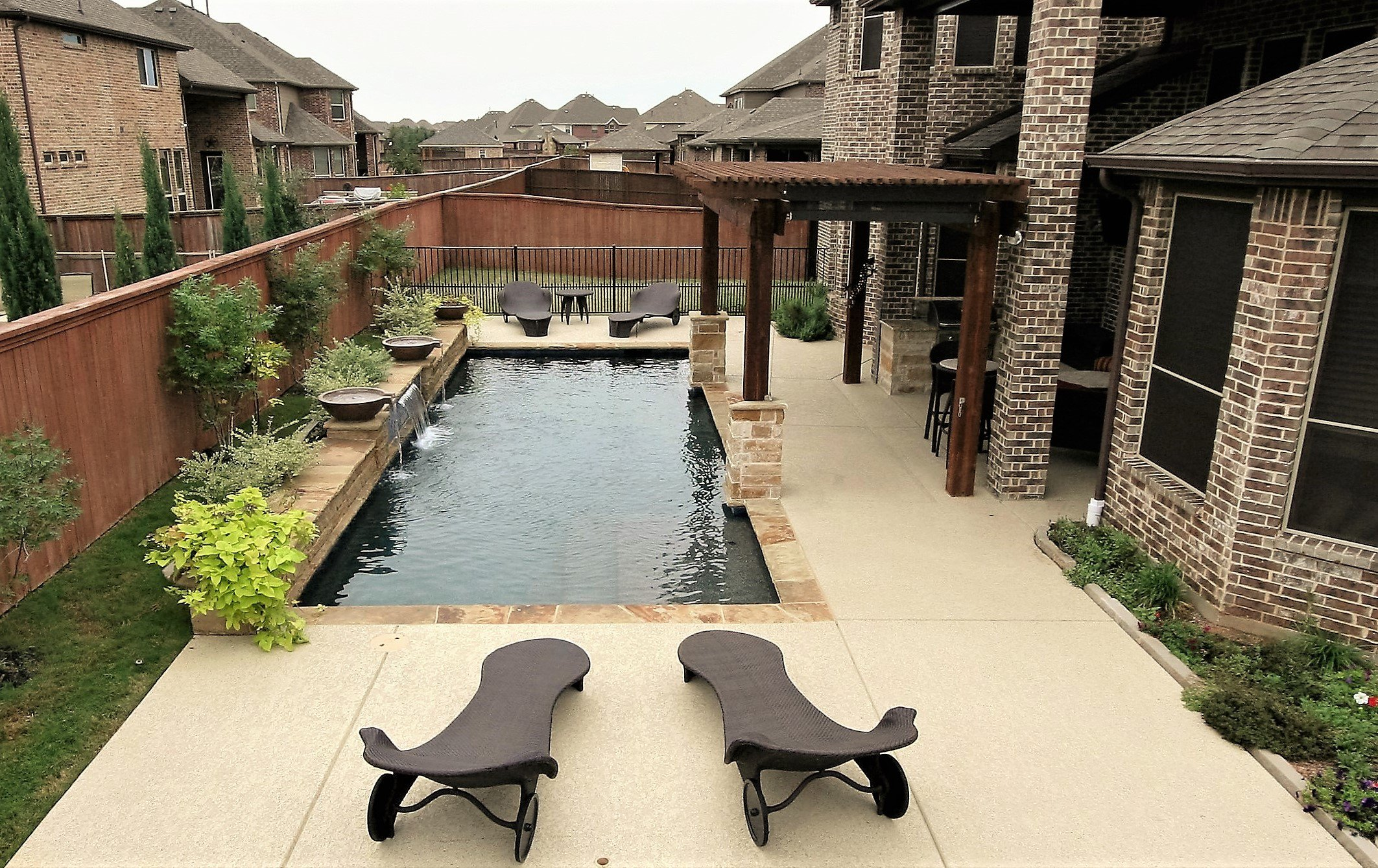 Traditional pool, Oklahoma Flagstone, Sundek, Wet Edge Midnight Sea plaster, Arbor, Outdoor kitchen, Wok water bowls, planter bowls, sheer descent, spa & Zodiac Equipment