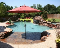 Free-form-pool-rock-beach-entry-with-umbrella-sleeve-deck-jets-spa-grotto-rock-weeping-walls-aggregate-decking-wet-edge-plaster-zodiac-polaris-equipment