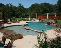 Free-form-pool-with-kiddie-pool-rock-beach-entry-grotto-rock-waterfall-deck-jets-retaining-wall-aggregate-decking-fire-pit-pebble-plaster-zodiac-equipment
