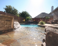 Free-form-pool-rock-beach-entry-flagstone-coping-raised-spa-with-stacked-rock-grotto-waterfall-white-plaster-zodiac-polaris-equipment