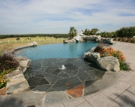 Free-form-vanishing-edge-pool-beach-entry-with-bubbler-and-pennsylvania-gray-flagstone-slide-waterfall-grotto-accent-boulders-deck-jets-zodiac-equipment