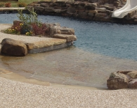 Free-form-pool-rock-beach-entry-with-accent-boulders-spa-rock-waterfall-interfab-diving-board-aggregate-decking-pebble-plaster-zodiac-equipment