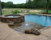 Free-form-pool-rock-beach-entry-with-bubbler-fountain-and-accent-boulders-spa-patterned-concrete-decking-skins-pattern-wet-edge-plaster-zodiac-equipment