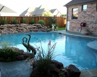 Freeform Pool; Rock Weeping Wall, Flagstone Coping, Slide, Planters, Wet Edge Plaster, Zodiac & Polaris Equipment