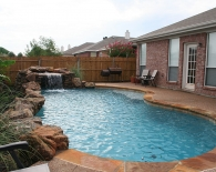 Freeform Pool; Rock Waterfall and Weeping Wall, Flagstone Coping, Aggregate Decking, White Plaster, Zodiac & Polaris Equipment