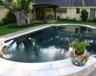 Traditional-pool-raised-water-feature-with-oreq-fountains-pre-cast-coping-aggregate-decking-wet-edge-plaster-zodiac-polaris-equipment