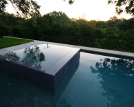Straight-line-pool-with-vanishing-edge-glass-tiled-spa-wet-edge-plaster-zodiac-equipment-and-deck-fountains