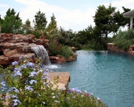 Free-form-vanishing-edge-pool-and-attached-spa-rock-waterfall-grotto-aggregate-decking-wet-edge-plaster-zodiac-equipment