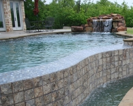 Free-form-vanishing-edge-pool-indoor-spa-tile-overflow-grotto-fountain-flagstone-coping-aggregater-decking-pebble-plaster-zodiac-equipment