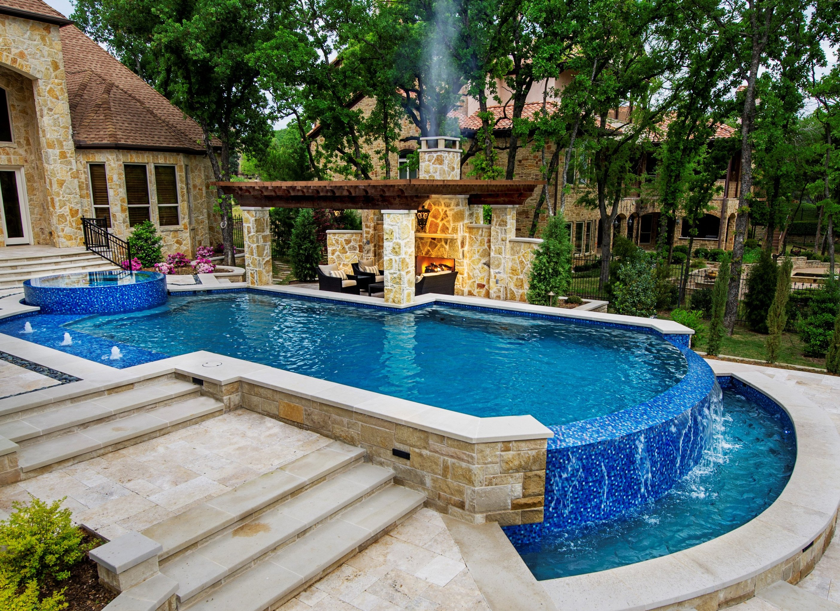 Negative Edge pool, Leuders coping, Travertine decking with Mexican pebble inlay, bubblers, Arbor with rock columns on edge of pool beam. Fireplace & Zodiac Equipment