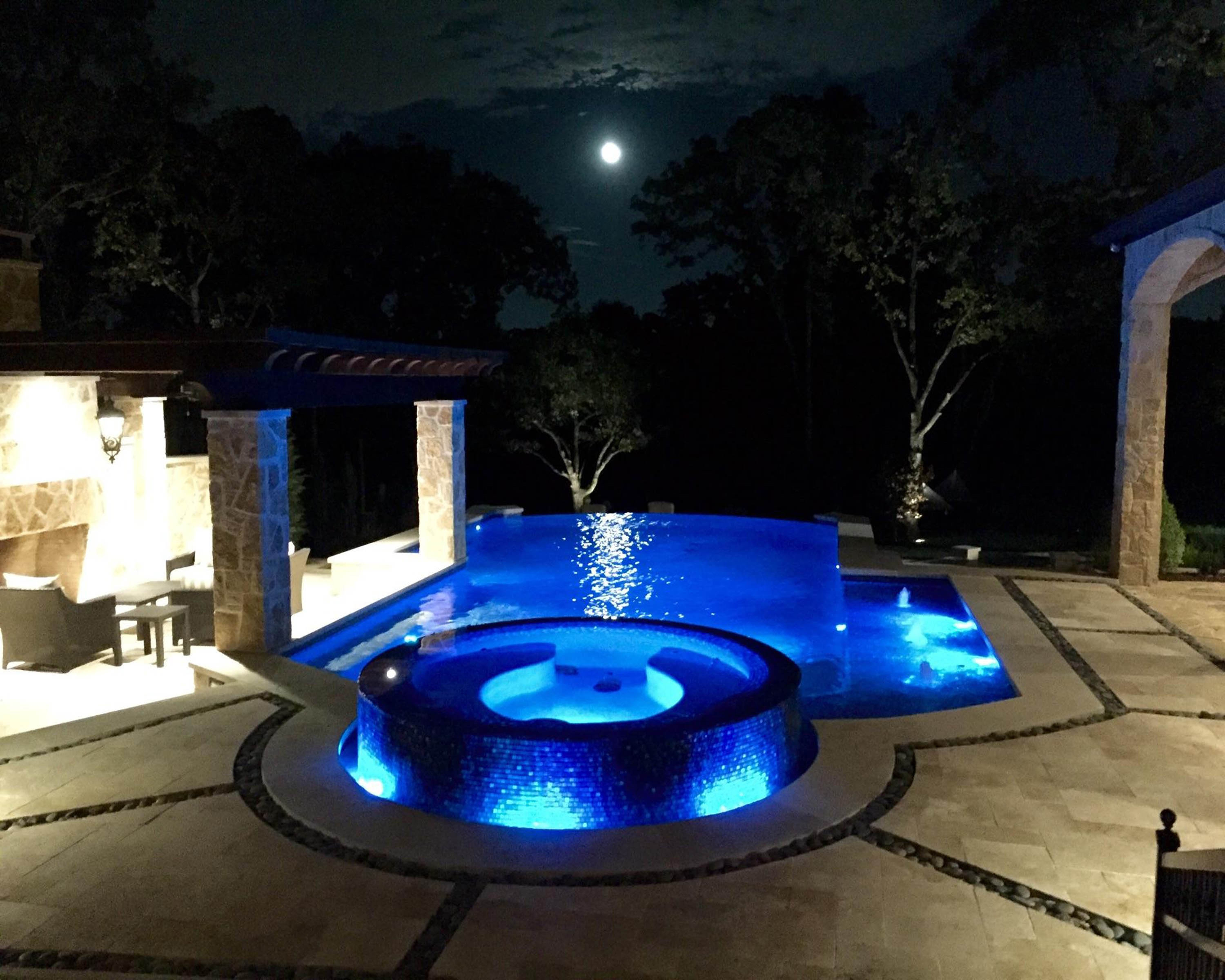 Negative Edge pool with 360 degree infinity edge spa, Travertine decking with Black Mexican pebble inlay. Glass tile. Bubblers, Wet Edge Indigo Blue plaster & Zodiac Equipment