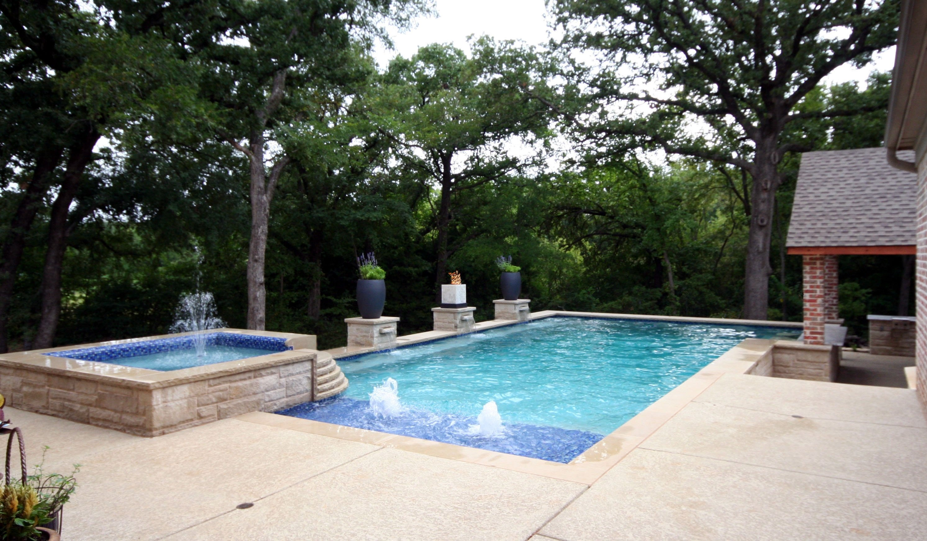 Traditional /Modern pool, Lueders coping, Sundek, Wet Edge Tahitian Blue plaster, Grand Effects Fire Feature, Rock Port fountains, Outdoor grill, Rock columns, large corner spa with rolled beam tile with fountain, Swim up granite bar with stools & Zodiac Equipment.