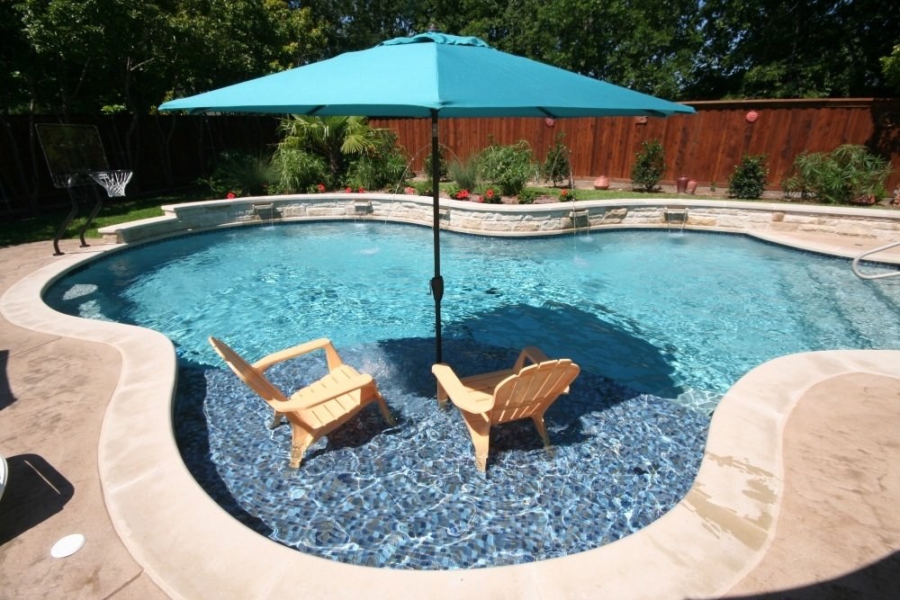 Freeform pool,Leuders coping, Arbor, Deck jets, raised wall with Rock ports, glass tile on tanning ledge Stamped concrete. Wing walls & Zodiac Equipment