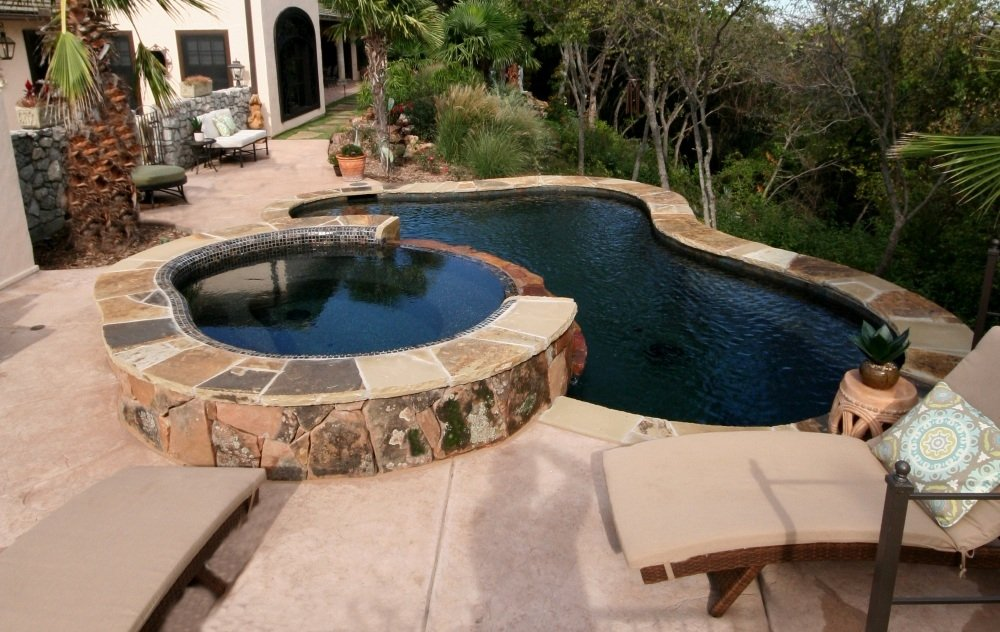 Freeform pool, Oklahoma flagstone, Stamped Concrete, Wet Edge Jet Black plaster, Spa with rolled beam tile with cascading spillway & Zodiac Equipment
